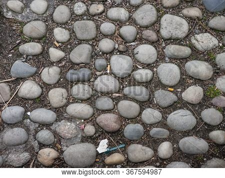 Old Worn Round Cobblestones Set Into The Ground On A Walkway With Scattered Discarded Cigarette Butt