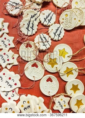 Assorted Shaped Hanging Christmas Decorations Scattered Over A Red Background With Bells And Medalli