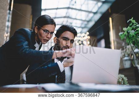 Focused Coworkers Surfing Laptop In Office In Lobby Of Hotel