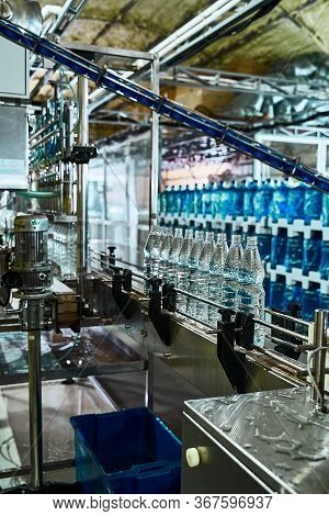 Pure Drinking Water Plant. Work Conveyor In The Enterprise. Liter Bottles On The Conveyor Are Filled
