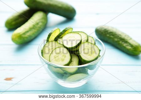 Fresh Cucumber Slices In Bowl On Blue Wooden Background. Top View