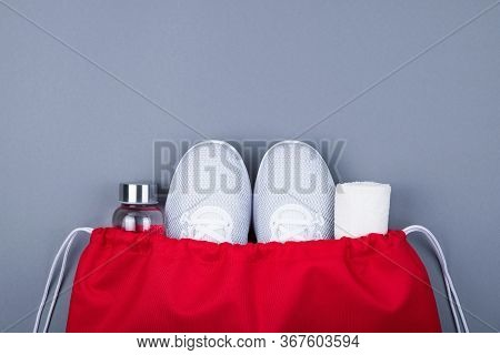 Top View Of White Sport Shoes Sneakers, Reusable Glass Water Bottle And Towel In Red Sport Bag On Gr
