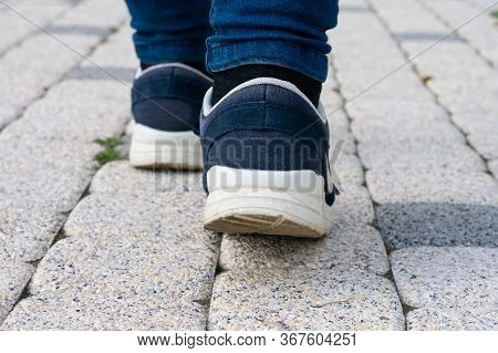 Feet In Running Shoes Are Walking Forward On Stony Road. Concept Of Leaving, Loneliness Or Passing A