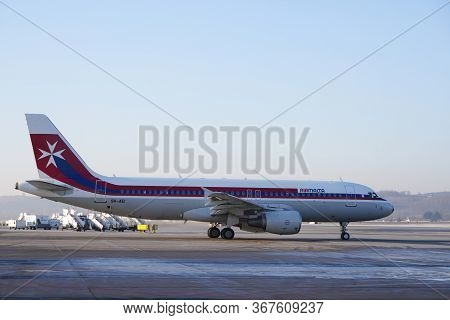 Air Malta Airbus A320-214, Nomber 9h-aei In Retro Scheme At The International Airport Against The Bl