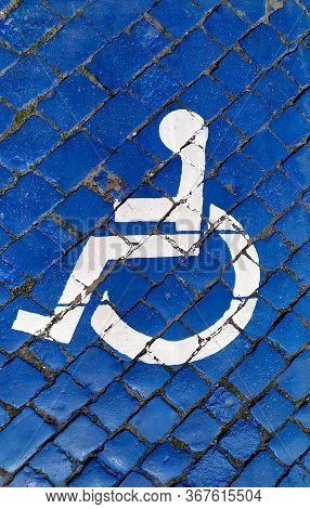 International Handicapped Symbol Painted In Bright Blue On A Paving Street Parking Space. Disabled H