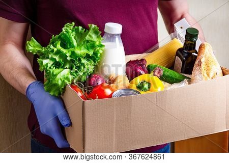 Volunteer In Gloves Holding Food In A Donation Cardboard Box With Various Food. Open Cardboard Box W