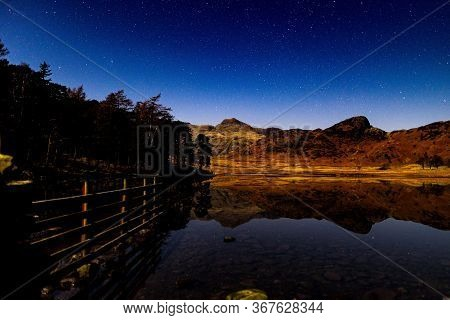 Blea Tarn On A Moonlit Night With The Hills Reflecting In The Tarn.
