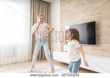 Two Sisters Having Fun Dancing In Living Room And Singing Karaoke, Happy Family Concept