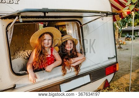 Little Girl In Straw Hat And Red Polka Dot Sundress And Pretty Long Haired Curly Baby Girl Sitting B