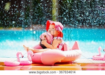Cute Baby Girl In Dark Pink Panama Hat Hugging Pink Rubber Flamingo Swimming Ring, Sitting In The Po