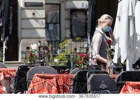 Vilnius, Lithuania - May 23 2020: Waitress With A Mask And Gloves Disinfecting The Table Of An Outdo