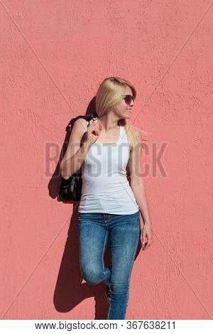 outdoor summer portrait of young blonde cheerful woman with sunglasses and white tank top against pink wall mock up tank top