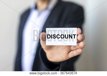 Discount Word On Sticker In Man's Hand With Blurring Background Of Man In Suit
