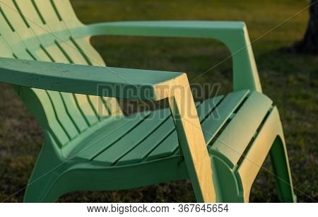 Closeup Of A Lime Green Plastic Resin Adirondack Lawn Chair Sitting On The Grass At Sunset.