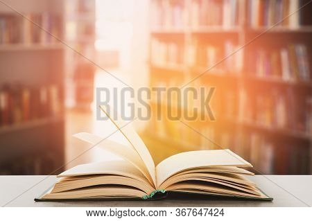 Open Hardcover Book On Table In Library