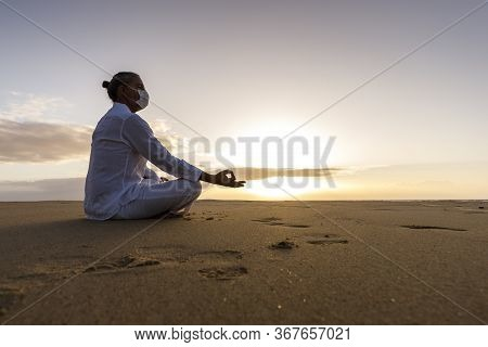 Meditating Man In Medical Mask In Lotus Pose On The Beach, Male Wearing Surgical Face Mask And White