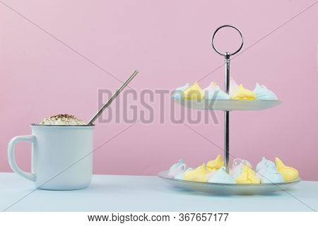 Small Blue, Yellow, And Pink Meringues Served On A Two Tier Serving Plate And A White Mug With Whipp