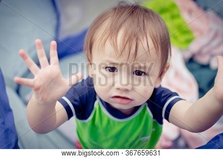 A Baby Boy Motioning That He Wants To Be Held