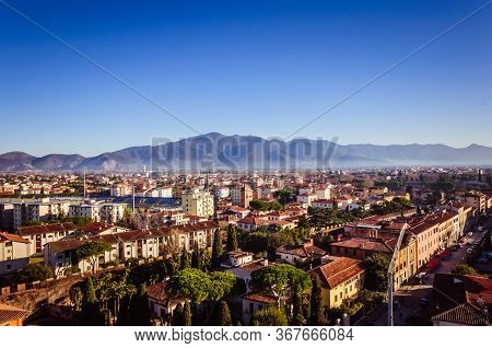 Beautiful Small City With Morning Fog And Mountains On The Background, Covered With Forest  And Unde
