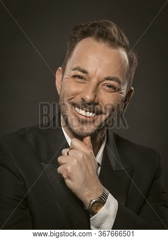 Well-dressed Businessman Toothy Smiles While Touching His Chin With His Hand. Portrait Of Handsome C