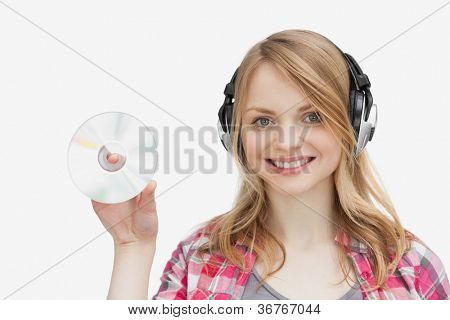 Woman holding a cd while wearing headphones against a white abckground