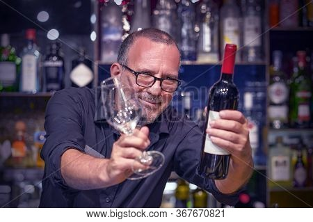 Elderly Bartender Holds A Bottle Of Red Wine And Wine Glasses In The Hotel Bar. Elderly Bartender Ma