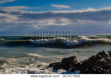 Storm And Storm In The Black Sea. Dark Storm Waves With A Cap Of Foam Beat Against The Rocks.