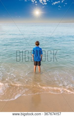 Young Boy Staring Our Towards To The Horizon With His Feet In The Surf And A Beautiful Blue Sea And