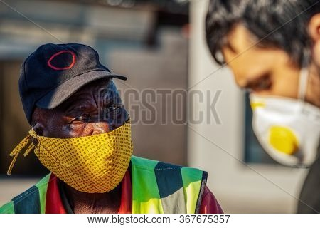 Caucasian man with a mask near an  old African worker dressed with a vest portrait