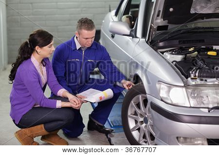 Mechanic showing the car wheel to a client in a garage