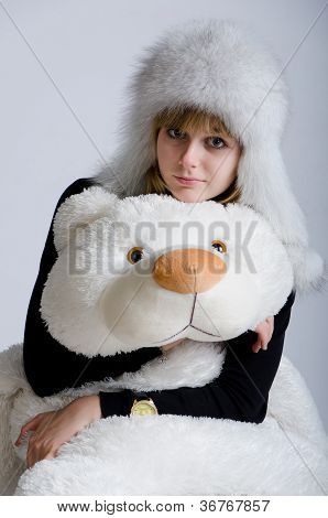 Girl In A White Fur Hat With A Toy Bear In A Studio