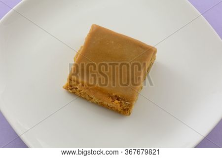 Toffee Flapjack Square Cake Bar On White Plate On Lavender Background