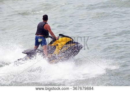 Young Man Running Waves On A Speeding Yellow And Black Jetski.