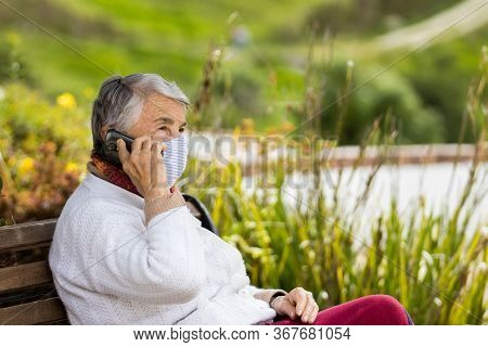Senior Woman Outdoors Using Her Cell Phone Wearing A Home Made Face Mask During The Coronavirus Quar