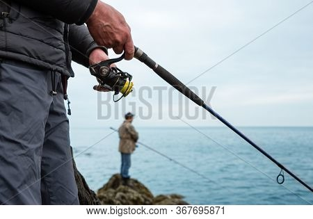 Fishermen catch salmon in the sea from the rocks