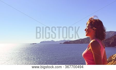 Mature Woman With Eyes Closed Relaxing On Sea Coast, Enjoy Breeze And Sunlight. Summer Holidays.