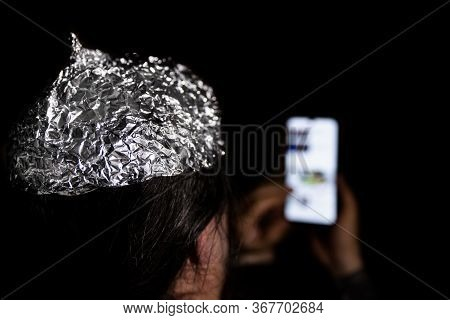 Man In The Dark Wearing A Tin Foil Hat, Smartphone In The Hand, Conspiracy Theory And Mind Control