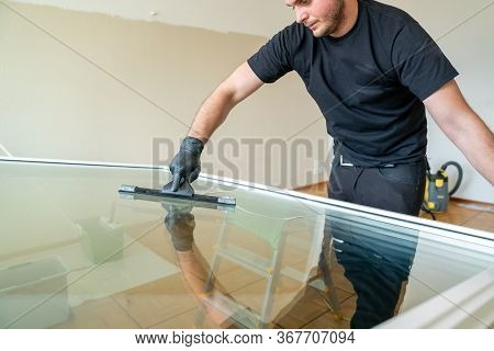 Professional Cleaner Using A Squeegee And Scraper To Clean A Large Apartment Window