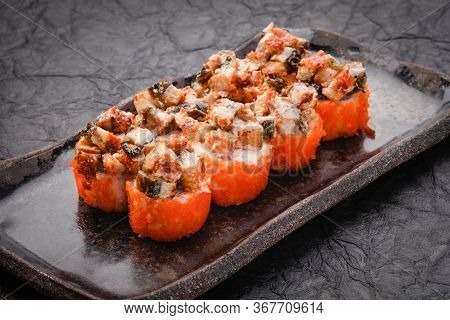 Sushi Set Served On Black Plate On Dark Background. Baked Maki Roll With Eel, Masago, Salmon, Cream