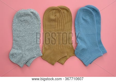 Short Socks Of Gray, Brown And Blue Top View. Cotton Socks For Sports On A Pink Background. Set Of 3