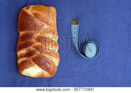 Tasty Bun Braid With A Golden Crust And A Centimeter Top View. Big Yeast Burger On A Blue Background