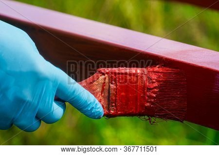 House Painter Paints Metal Structures. Protective Coating Of Steel Closed Profiles With Primer Iron
