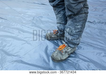 Worker In Dirty Uniform And Shoes With Orange Laces Is Staying In Construction Site. Concept Of Diry