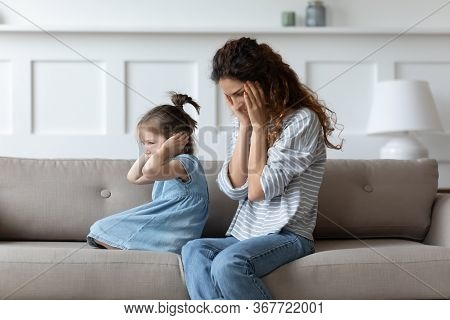 Stubborn Spoiled Little Girl Covering Ears, Ignoring Hopeless Upset Mother