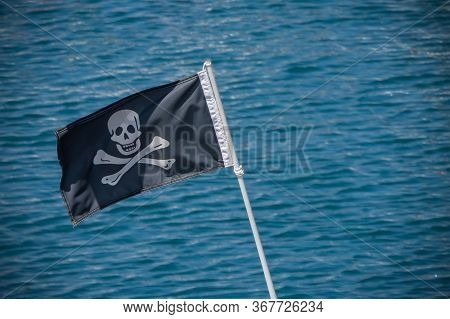 Jolly Roger Black Pirate Flag With Human Skull On Blue Sea Background