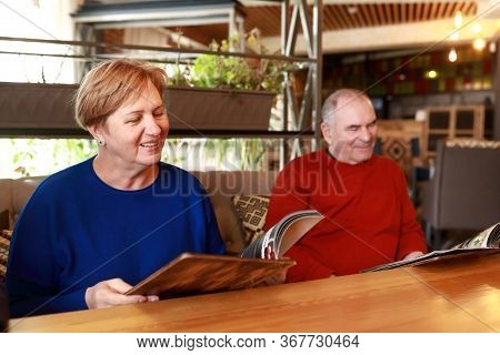 Portrait Of Senior Couple With Menu Books In Restaurant