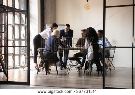 Diverse Employees Team Engaged In Teamwork In Modern Boardroom