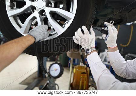 Mechanic Repairing Wheels, Seasonal Tire Change. Running Diagnostics At Service Station. Assembly Ti