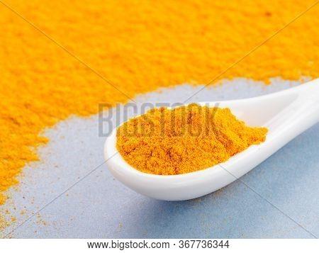 Turmeric Powder Or Curcuma Longa And White Spoon With Turmeric Powder On Gray Background. Copy Space
