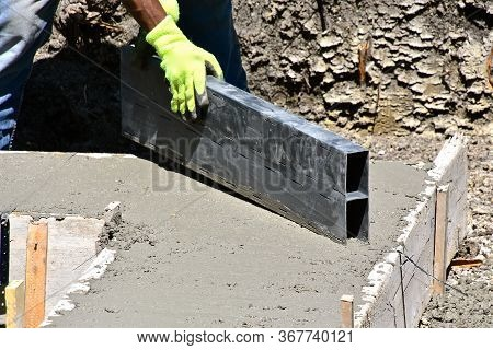 A Concrete Workers Smooths And Levels The Wet Concrete Of  A Basement Footing Which Has Just Been Po